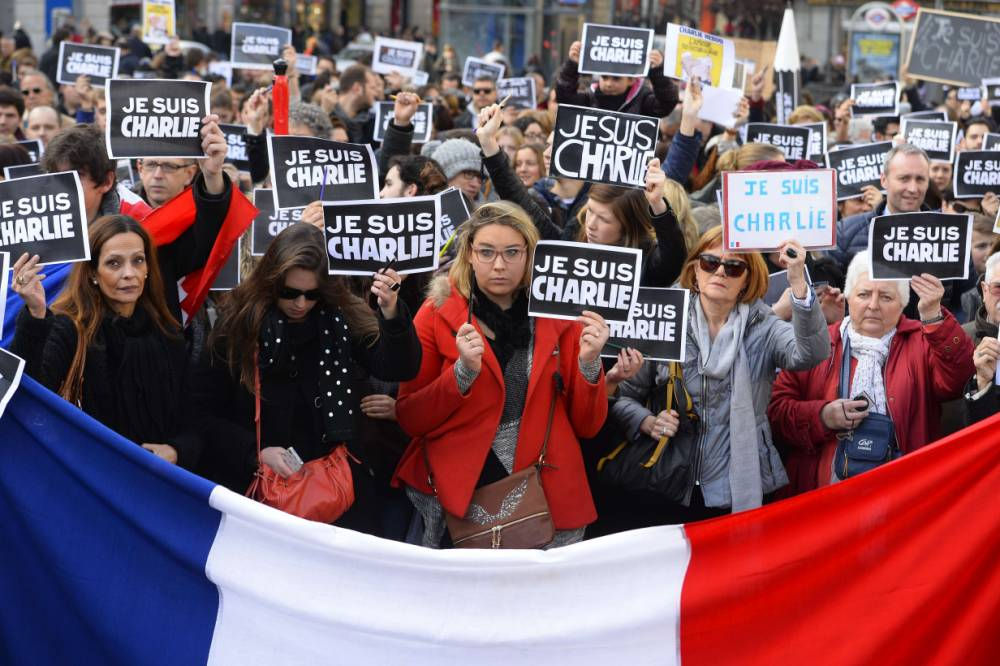 "People hold placards reading in French ""I am Charlie"" behind a french flag during a public show of solidarity at Plaza del Sol in Madrid on January 11, 2015 and to protest against three days of bloodshed triggered by an attack on French satirical weekly Charlie Hebdo that left 12 dead.  More than a million people and dozens of world leaders are expected to participate in a massive and historic march in Paris today in solidarity with the victims of the Islamist attacks that killed 17 and deeply shook the country.  AFP PHOTO / GERARD JULIENGERARD JULIEN,GERARD JULIEN/AFP/Getty Images"