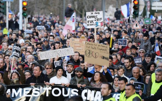 """People hold a banner reading """"Nous sommes tous Charlie"""" (We are all Charlie) during a Unity rally Marche Republicaine on January 11, 2015 in Strasbourg, eastern France, in tribute to the 17 victims of the three-day killing spree. The killings began on January 7 with an assault on the Charlie Hebdo satirical magazine in Paris that saw two brothers massacre 12 people including some of the country's best-known cartoonists and the storming of a Jewish supermarket on the eastern fringes of the capital which killed 4 local residents. AFP PHOTO / PATRICK HERTZOGPATRICK HERTZOG/AFP/Getty Images"""
