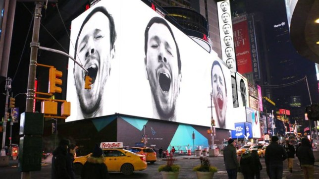 CREDIT INDIVIDUALS & add Rex Features  Mandatory Credit: Photo by Sebastian Errazuriz Studio/REX (4376266b)  The face of Sebastian Errazuriz appears on electronic billboards  Artist tries to trigger contagious yawning in Times Square, New York, America - 13 Jan 2015  FULL COPY: http://www.rexfeatures.com/nanolink/pt9t VIDEO (test yourself, try to NOT yawn): http://youtu.be/iIrpKN6D3gc  An artist is attempting to trigger contagious yawning in New York's Times Square.  Sebastian Errazuriz has created 'A Pause in the City That Never Sleeps', a video that consists of a continuous yawn on loop, which will be shown on Times Square's electronic billboards from 11:57 pm to midnight each night in January.  The yawning character - actually Chilean-born, London-raised, New York-based Sebastian himself - appears on multiple screens as a bored, omnipresent head looking down at the passing people from between product billboards and advertisements. As yawns are contagious, the masses of people looking up at the screens will inadvertently feel inclined to stop and yawn.