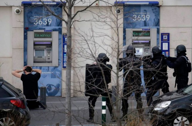 A suspect in a hostage taking situation is detained by members of special French RAID forces outside the post offices in Colombes outside Paris, January 16, 2015.  REUTERS/Philippe Wojazer (FRANCE - Tags: POLITICS CRIME LAW TPX IMAGES OF THE DAY)
