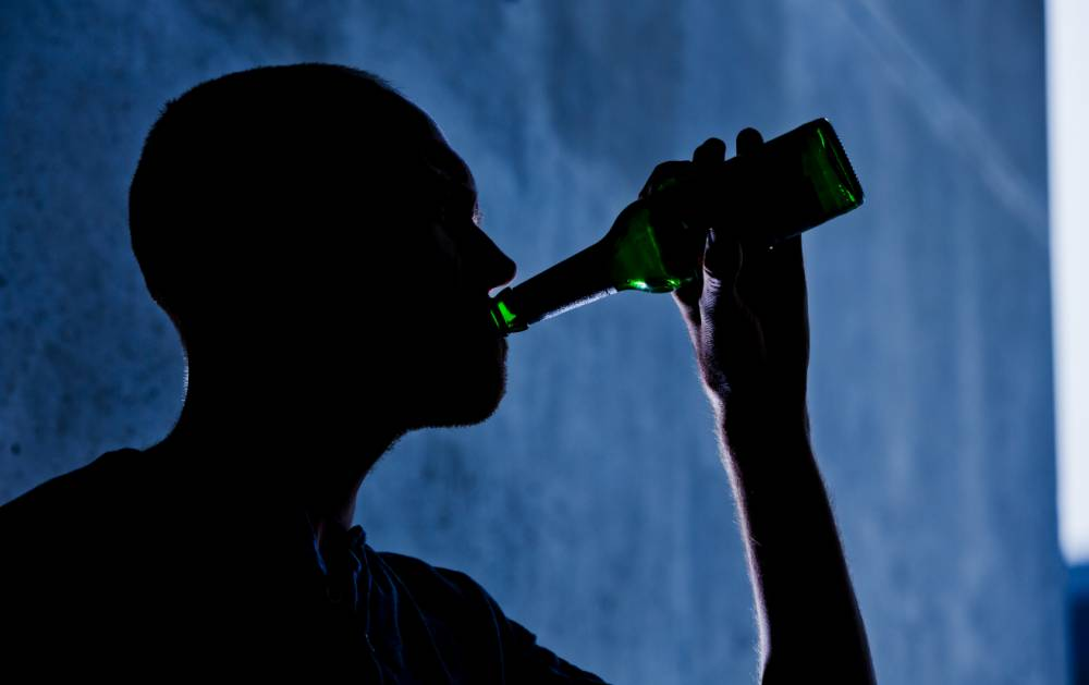 BERLIN, GERMANY - AUGUST 13: (EDITOR'S NOTE: In this photo illustration) A young man is seen drinking from a beer bottle on August 13, 2014 in Berlin, Germany.  (Photo Illustration by Michael Gottschalk/Photothek via Getty Images)