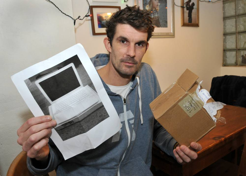 Paul Barrington with the picture of a computer he received after winning an auction on eBay. See SWNS story SWCOMPUTER: A surfer who sold his last board to buy a laptop is questioning his luck after he was sent a picture of a computer instead of the real thing. Paul Barrington, 38, from Ilfracombe, has been in and out of hospital with a lung condition. Unable to surf or continue his physically demanding job in child care, he sold his beloved surfboard and ordered an Apple MacBook on eBay. He plans to launch a new career as a wedding DJ and needs the computer to run music software.