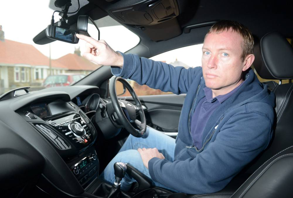 """Wayne Clinning of Morecambe pictured with his Ford car and it's dashboard camera system. See SWNS story SWCAMERA: A motorist was furious when a dashboard camera revealed reckless garage mechanics had been driving his car almost double the legal limit - reaching speeds of 118mph. Baffled Wayne Clinning, 42, took his car in for a service and new tyres and also asked workers at the official Ford garage to check the speedometer and the tracking. But when he got his Ford Focus ST back he claims half a tank of fuel had been used so activated the dashboard camera when he returned the vehicle for more repairs. He couldn't believe it when he got back his sporty car and watched footage which appeared to show a mechanic """"joyriding"""" his car - reaching speeds of 118mph. 13 February 2015"""