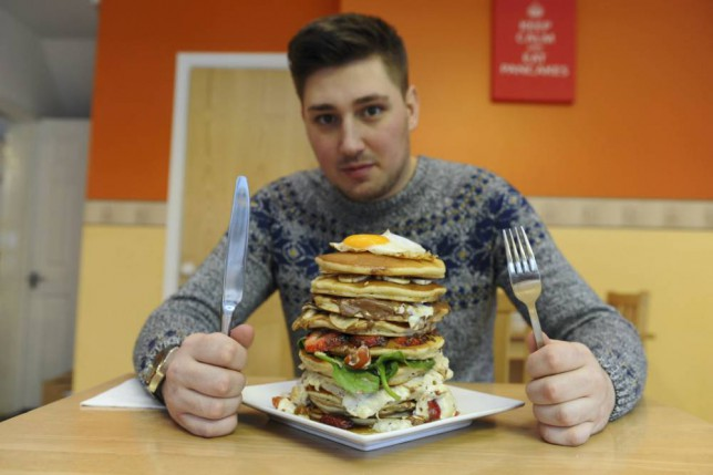 Jacon Moss with the pancake tower. The ultimate pancake cake eating challenge has been launched by the Pancake Corner in Urmston, Manchester. For this Shrove Tuesday customers can attempt to take on ëThe Beastí a pancake tower consisting of a combination of 10 bizarre layers of savoury and sweet filling which has to be eaten in under 10 minutes. Instead of tucking into the conventional maple syrup or sugar and lemon pancake stack foodies can try their weird gut busting 12 inch tall pancake tower of six savoury layers and 4 sweet layers in just 10 minutes to succeed. The bottom layer is an American style pancake topped with Italian tomato sauce and cheese, followed by a layer of Cajun chicken and BBQ sauce, and a layer of marinated chicken mayo and black pepper and also includes a layer of spinach, tomato and cheese and also a pancake topped with salami.  If this wasnít enough, piled atop these hearty savoury pancakes are four rich layers of strawberry and Nutella, peanut butter and slice banana, hazelnut, slice banana and toffee sauce and a mix of milk and white chocolate buttons and the icing on the pancake is a fried egg smothered in maple syrup.