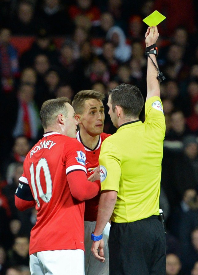 Manchester United's Belgian midfielder Adnan Januzaj (2nd L) is booked by referee Michael Oliver (R) for simulation during the FA Cup quarter-final football match between Manchester United and Arsenal at Old Trafford in Manchester, north west England, on March 9, 2015. AFP PHOTO / OLI SCARFF RESTRICTED TO EDITORIAL USE. No use with unauthorized audio, video, data, fixture lists, club/league logos or live services. Online in-match use limited to 45 images, no video emulation. No use in betting, games or single club/league/player publications. OLI SCARFF/AFP/Getty Images