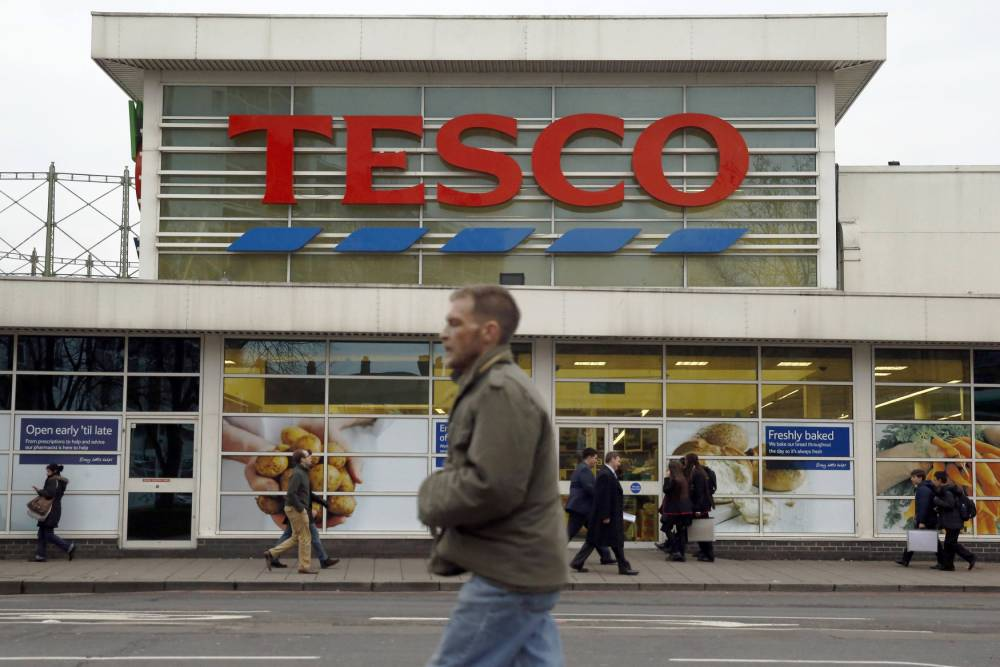 Pedestrians pass a Tesco supermarket in London January 5, 2015. Britain's biggest grocer Tesco plans to sell assets and cut hundreds of millions of pounds of costs to fund lower prices in store as part of its plan to fight back from the biggest crisis in its 95-year-history. Seeking to recover from four profit warnings and an accounting scandal last year, new Tesco boss Dave Lewis on Thursday unveiled his plan alongside a trading update showing a marked improvement in trading. Photograph taken on January 5, 2015. REUTERS/Luke MacGregor  (BRITAIN - Tags: BUSINESS FOOD)