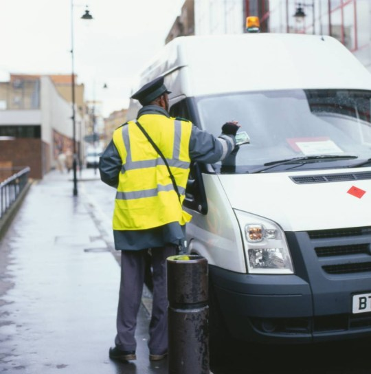 Traffic warden putting a parking ticket on a white van in London, England, UK.   B10MAM  Image shot 04/2008. Exact date unknown.