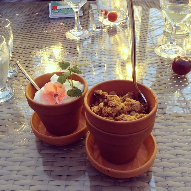 Two small flower pots with apple crumble and cream in