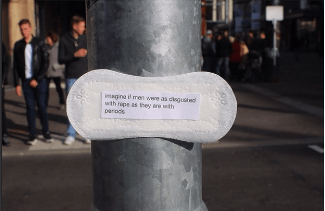 A sanitary towel with a feminist  slogan stuck on a lamp post