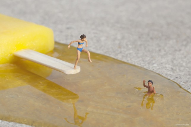 A tiny woman jumps off an ice lolly stick while a man swims in the melted ice