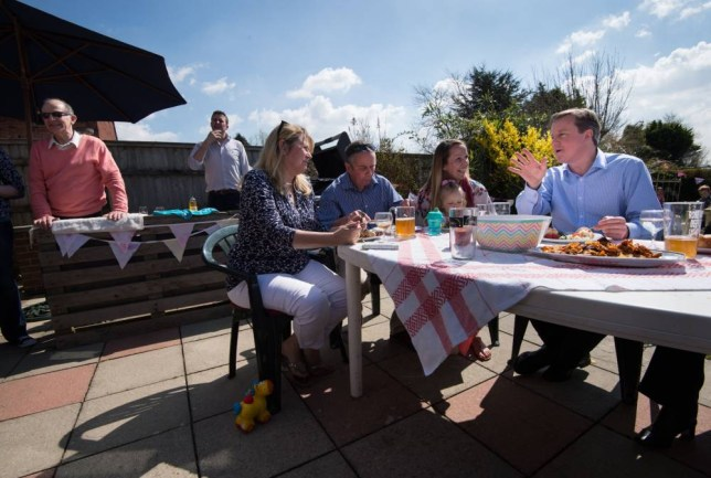 Prime Minister David Cameron (right) eats lunch in a garden with the Docherty family from Poole, Dorset, during a visit to the westcountry, as part of his 2015 general election campaign. PRESS ASSOCIATION Photo. Picture date: Monday April 6, 2015. See PA story ELECTION Main. Photo credit should read: Stefan Rousseau/PA Wire