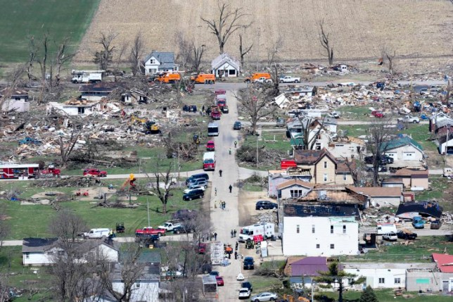 People survey, on Friday, April 10, 2015, the damage caused by a tornado the night before, in Fairdale, Ill. Damage survey teams were working Friday to officially determine the strength of the tornado system and extent of the damage. (AP Photo/Chicago Tribune, Armando L. Sanchez)