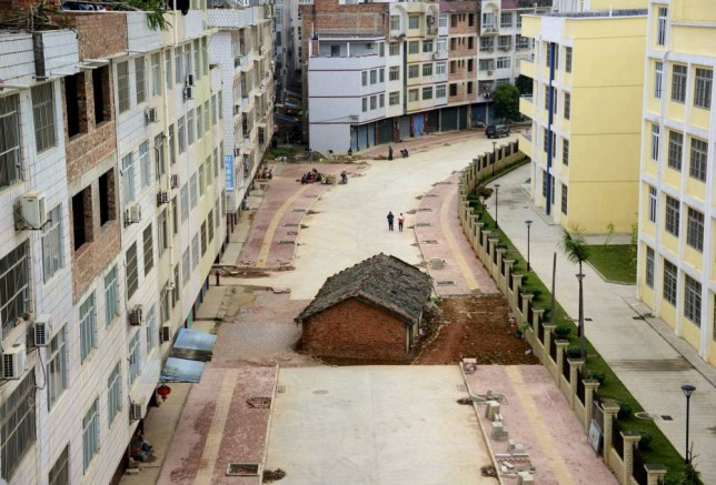 """A """"nail house"""", the last building in the area, sits in the middle of a road under construction in Nanning, Guangxi Zhuang Autonomous Region April 10, 2015. According to local media, the owner of the house didn't reach an agreement with the local authority about compensation of the demolition. Picture taken April 10, 2015. REUTERS/Stringer CHINA OUT. NO COMMERCIAL OR EDITORIAL SALES IN CHINA      TPX IMAGES OF THE DAY"""