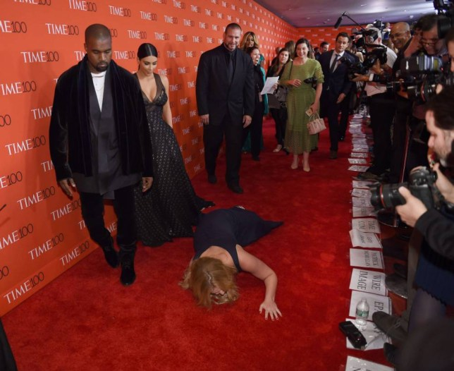 Honoree and comedian Amy Schumer pretends to trip and fall on the floor  in front of honorees Kim Kardashian and Kanye West as they attend the Time 100 Gala celebrating the Time 100 issue of the Most Influential People at  The World at Jazz at Lincoln Center on April 21, 2015 in New York.    AFP PHOTO /  TIMOTHY  A. CLARYTIMOTHY A. CLARY/AFP/Getty Images
