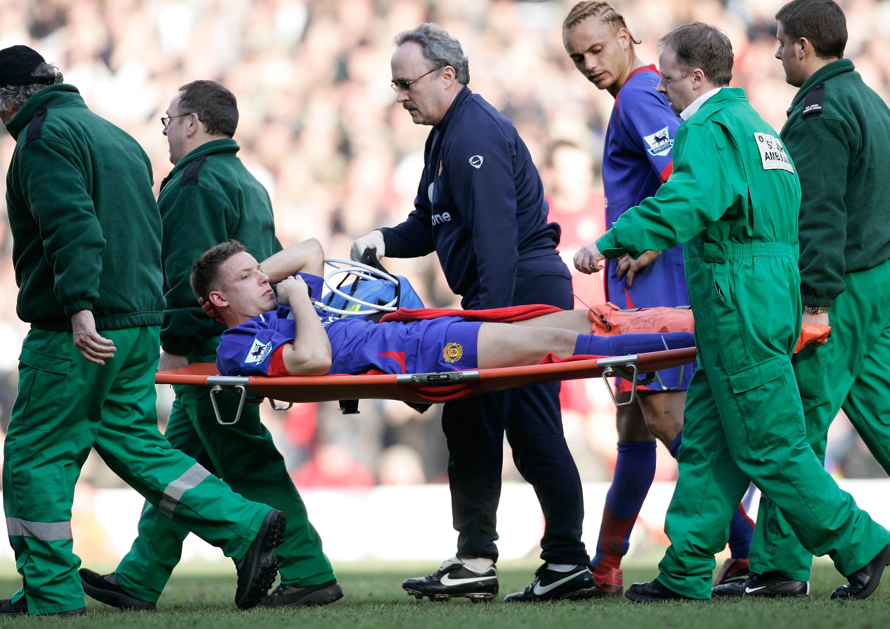 ALAN SMITH IS TAKEN OFF AFTER BREAKING HIS LEG IN THIS INCIDENT.