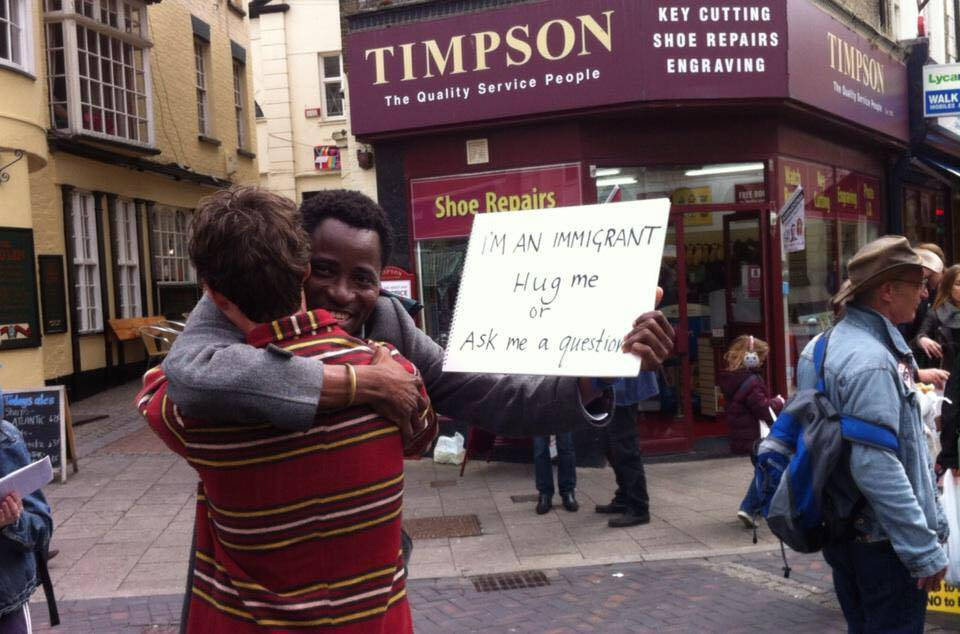 HIV positive immigrant holds 'hug me' sign next to Ukip campaign tent