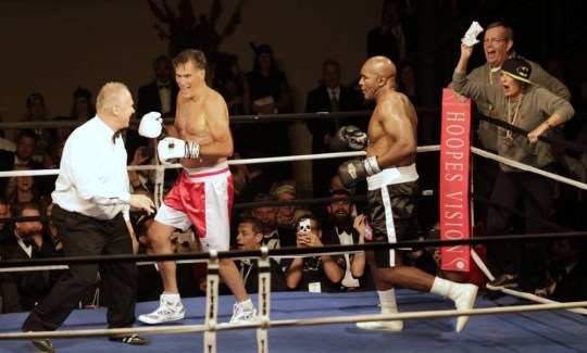 """SALT LAKE CITY, UT - MAY 15: Mitt Romney runs from Evander Holyfield after knocking him down during a fight in a charity boxing event on May 15, 2015 in Salt Lake City, Utah. The event was held to raise money for  """"Charity Vision"""" a charity that aims to restore sight to the blind and visually impaired. (Photo by George Frey/Getty Images)"""