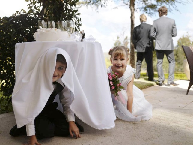 Pageboy and flowergirl(6-7) hiding underneath table
