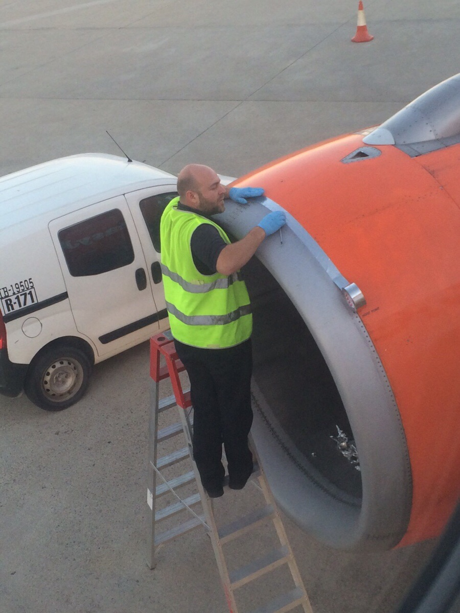 Terrified passenger takes photo of TAPE being stuck on plane engine shell moments before take off