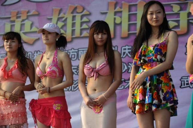 This photo taken on June 25, 2011 shows a group of Chinese women parading in their suitsuits during a matchmaking event for wealthy men, with assets over 30 million yuan or make over one million yuan in annual income, and must also pay 99,999 yuan for the entrance ticket, held at the East Lake beach in Wuhan, central China's Hubei province. China's wealthiest are getting richer, with the minimum amount needed to make the top 400 rising to 425 million USD from 300 million in 2010.     CHINA OUT      AFP PHOTO (Photo credit should read STR/AFP/Getty Images)