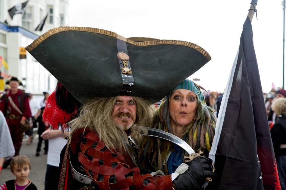 "14,155 pirates gather on the promenade in Penzance, missing out on reclaiming the Guiness World Record for most pirates in one place by just 77 people. See SWNS story SWPIRATE;  A probe has been launched after a council spent more than £50,000 on a doomed world record bid - for the biggest ever gathering of PIRATES.  The event generated huge excitement when more than 14,000 in pirate fancy dress gathered in Penzance promenade - but the Cornish town missed the official Guinness World Record by just 77.  That disappointment has now turned to anger after the inflated cost of hosting so many pirates has emerged - at the time the council is having to make huge cuts in its services.  It has now been revealed that nearly three times the agreed £20,000 budget was spent by the town council on the pirate fancy dress event which was held as part of its 400-year charter celebrations in 2014.  The final bill has came in at £56,056.  Mayor David Nesbesnuick has described the overspend as a ""sorry business"" and promised full ""transparency.""  In a letter, sent to all town councillors, he promised a full and public investigation. 12 June 2015"