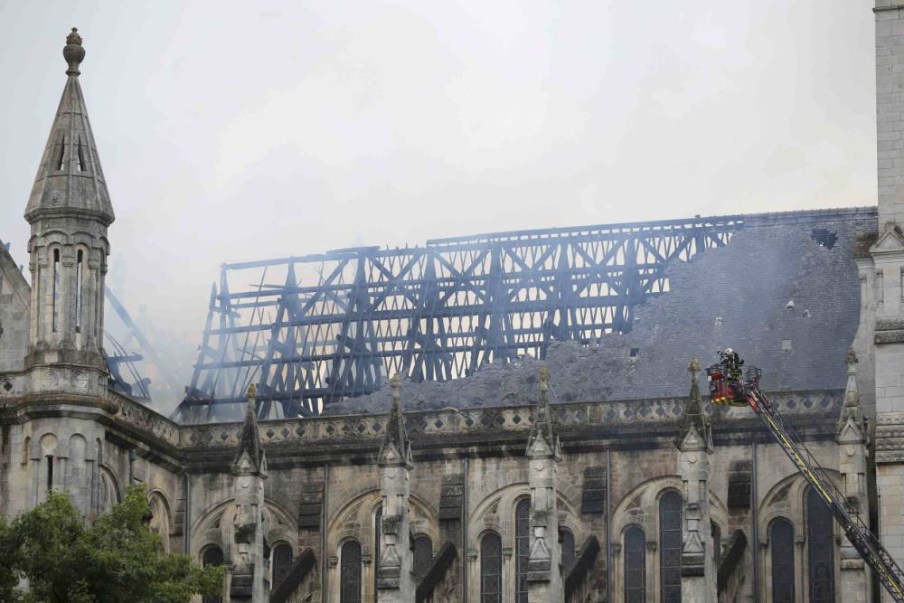 French firefighters try to extinguish the fire that damaged the roof of the Saint Donatien Basilica in Nantes, western France, June 15, 2015.  REUTERS/Stephane Mahe