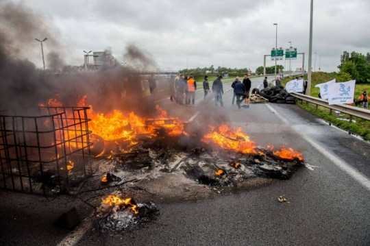 Striking employees of the French company My Ferry Link, a cross-channel ferry service, stand in front of tyres set on fire as they block the access to the Channel Tunnel on June 23, 2015 in Calais, northern France. AFP PHOTO PHILIPPE HUGUENPHILIPPE HUGUEN/AFP/Getty Images