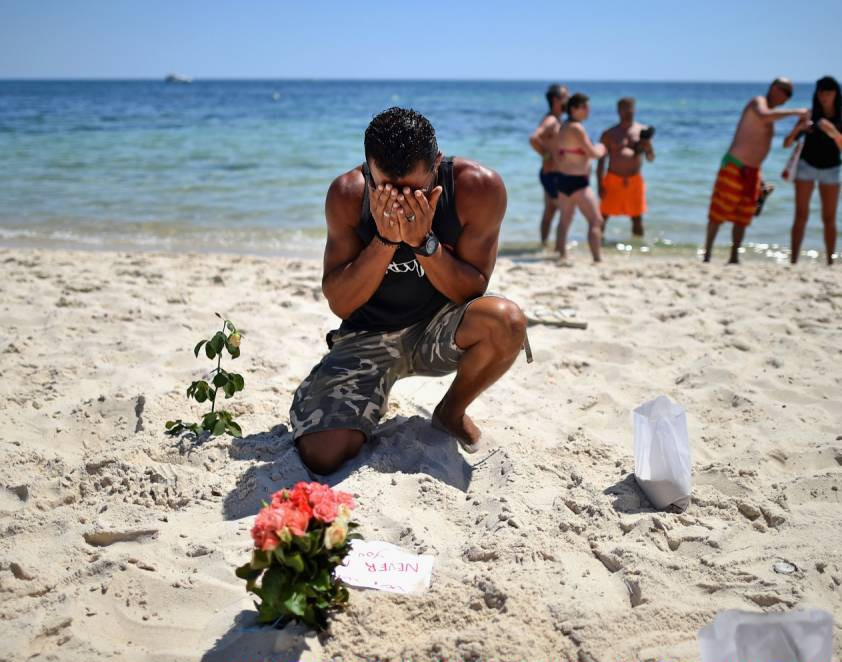 SOUSSE, TUNISIA - JUNE 28:  A man prays after laying flowers on Marhaba beach where 38 people were killed on Friday in a terrorist attack on June 28, 2015 in Souuse, Tunisia. Sousse beaches remain quiet following the Tunisia beach attack which left 38 dead, including at least 15 Britons. Around 1,000 tourists returned to the UK with more set to follow in the coming days.  (Photo by Jeff J Mitchell/Getty Images)