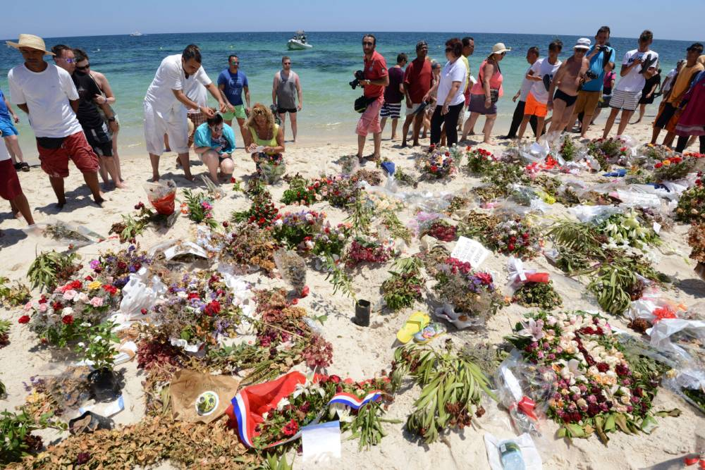 Tourists and Tunisians take part in a ceremony on July 3, 2015, in memory of those killed the previous week by a jihadist gunman in front of the Riu Imperial Marhaba Hotel in Port el Kantaoui, on the outskirts of Sousse south of the capital Tunis. Tunisia has arrested eight people in connection with last week's jihadist massacre at the seaside resort, as the remains of more slain Britons were flown home on July 2. AFP PHOTO / FETHI BELAIDFETHI BELAID/AFP/Getty Images