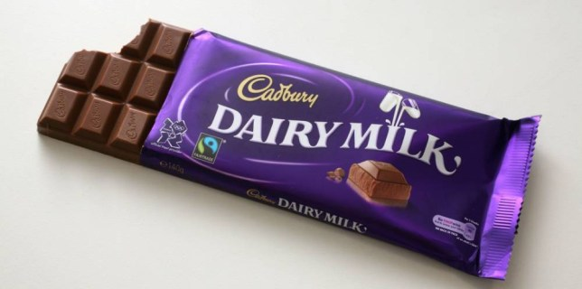A bar of Cadbury Dairy Milk chocolate in it's wrapper with a bite taken out of it.