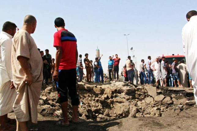 epa04851788 Iraqis gather around a hole caused by a truck bomb attack a day earlier at Khan bani Saad town, eastern Baghdad, Iraq, 18 July 2015. At least 120 people were killed and 130 people others were wounded in a car bombing claimed by the Islamic State (IS) jihadist terror militia at a busy market in Iraq's eastern province of Diyala, Muthana al-Tamimi the governor of Diyala province said. The explosion occurred while locals were gathering to celebrate the Muslim festival of Eid al-Fitr, which marks the end of the fasting month of Ramadan. Local authorities cancelled the Eid celebrations and declared three days of mourning for the victims.  EPA/STR
