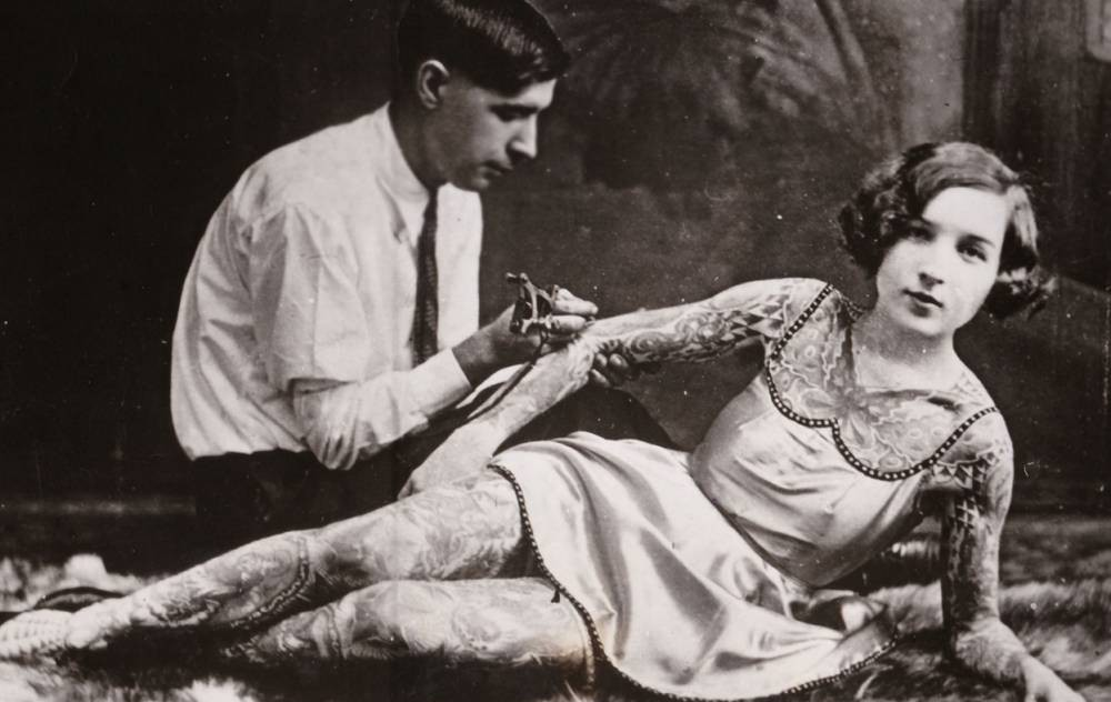 "MANDATORY CREDIT: Laurence King/REX Shutterstock  Mandatory Credit: Photo by Laurence King/REX Shutterstock (4909116f)  Woman getting tattooed in late 1920s  ""100 Years Of Tattoos"" book - Jul 2015  FULL BODY: http://www.rexfeatures.com/nanolink/qoke  A fascinating new book documents tattoo culture and its journey into the mainstream.  Author David McComb's '100 Years Of Tattoos' analyses the many cultures and sub-cultures associated with permanent ink.  Over the past century tattoo culture has emerged from the underground and hit the mainstream; from body art's early association with sailors, convicts and side-show acts to the current adoption of tattoo culture among celebrities, via the tattoo renaissance of the 1970s."