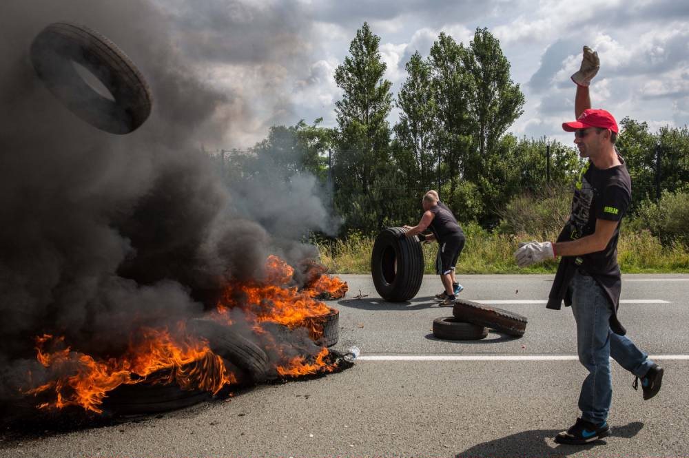 CALAIS, FRANCE - JULY 31:  Ferry workers burn tyres on both lanes of a road leading to the port of Calais on July 31, 2015 in Calais, France.  Employees of My Ferry Link blocked the key route leading to the port as part of an ongoing dispute over job losses.  Strike action and daily attempts by hundreds of migrants to enter the Channel Tunnel and onto trains heading to the United Kingdom is causing delays to passenger and freight services across the channel.  British Prime Minster David Cameron has announced that extra sniffer dogs and fencing are to be sent to Calais and land owned by the Ministry of Defence is to be used as a lorry park to ease congestion near the port of Dover in Kent.  (Photo by Rob Stothard/Getty Images)