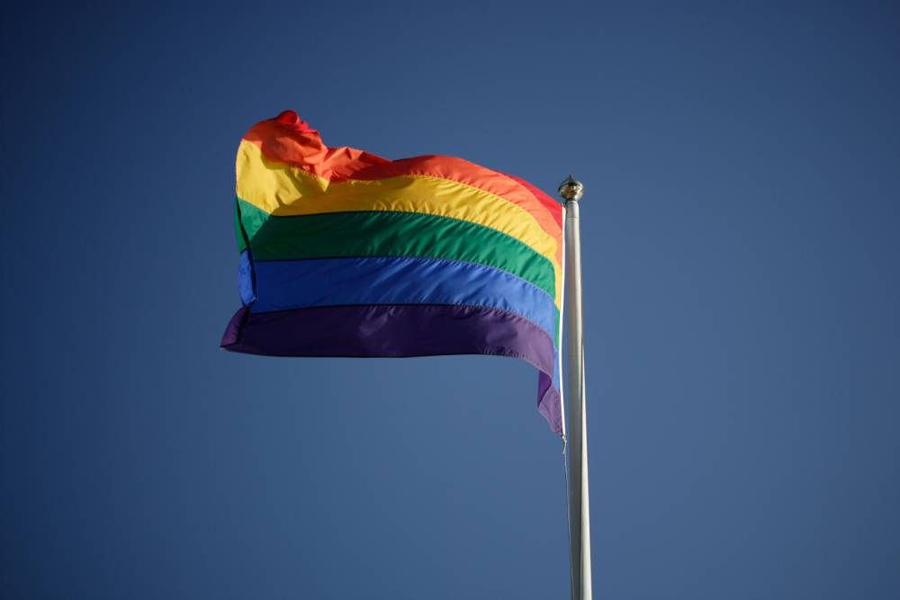 AG4PH4 Rainbow flag fluttering in the wind on a flagpole Gay symbol