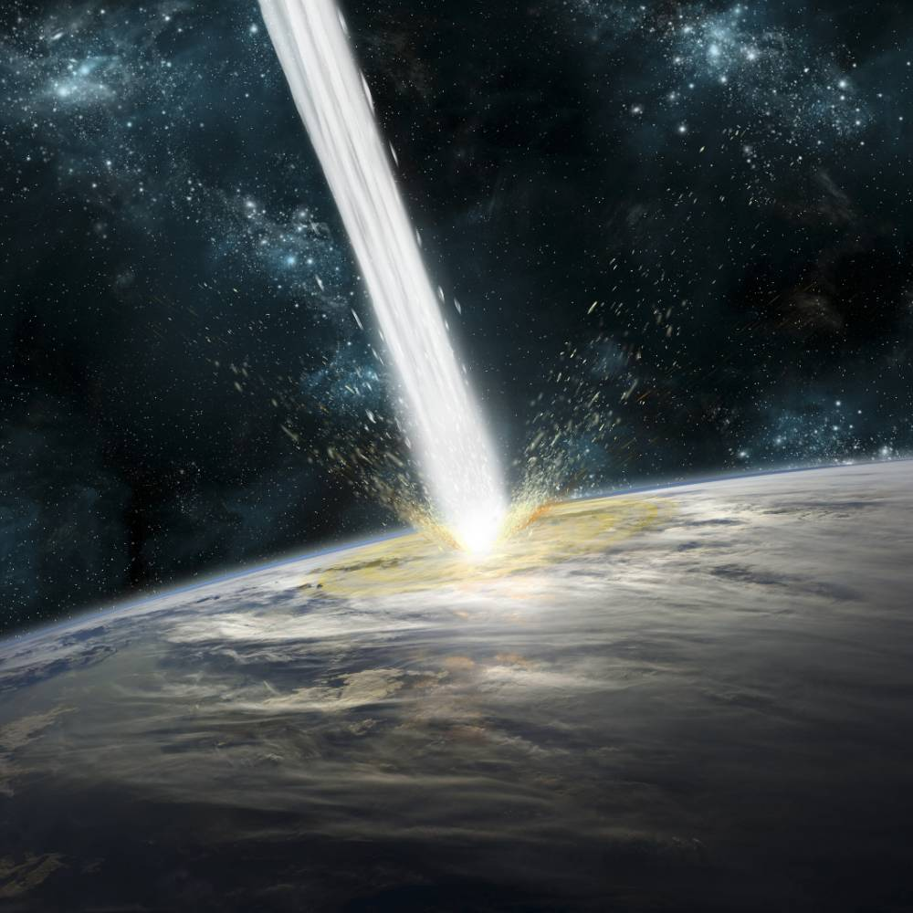 A comet strikes Earth. Clouds cover an ocean area of the planet. Stars and nebula serve as background.