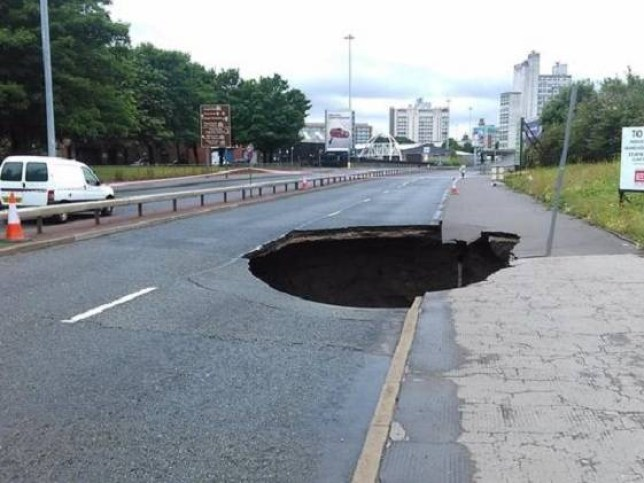 A giant 40ft deep hole has opened up on the Mancunian Way - with fears the road could be shut for weeks.nTraffic was halted in both directions on Friday morning after the crater - measuring at least 15 feet - appeared at the Ancoats end of the busy commuter route.nA giant 40ft deep hole has opened up on the Mancunian Way - with fears the road could be shut for weeks.