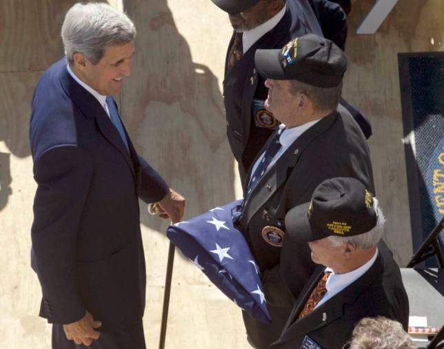 U.S. Secretary of State John Kerry greets the three Marines who lowered the flag at the U.S. Embassy's closing in 1961, and who have returned to raise the Stars and Stripes again, in a flag raising ceremony at the newly opened embassy, in Havana, Cuba, Friday, Aug. 14, 2015. (AP Photo/Ramon Espinosa)