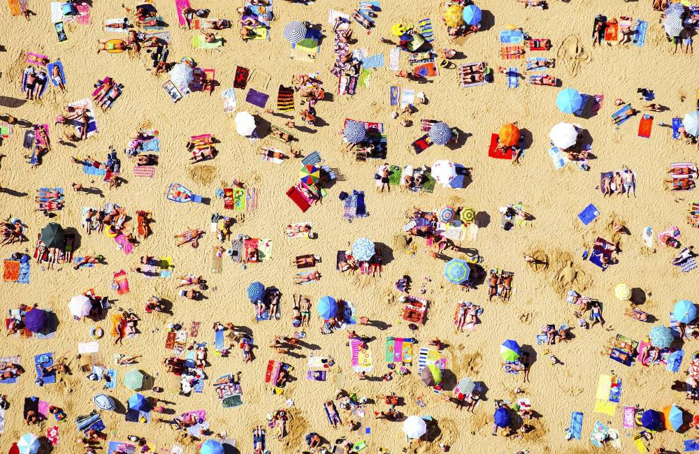"MANDATORY CREDIT: Tommy Clarke/REX Shutterstock. Only for use in this story. Editorial Use Only. No books, advertising or merchandising without photographer's permission.. Mandatory Credit: Photo by Tommy Clarke/REX Shutterstock (4901037p).. An aerial photo of a crowded beach in St Tropez.. Aerial photographs of St Tropez, France - 16 Aug 2014.. FULL COPY: http://www.rexfeatures.com/nanolink/qngo A photographer has shot a series of stunning aerial photographs of St Tropez. London-based photographer Tommy Clarke, 28, has become known for his daredevil tactics that include hanging out of the side of a helicopter to capture the perfect aerial shot. Incredible beaches, colourful parasols, yachts and turquoise sea can be seen in the photos. The aerial shots challenge perceptions, and objects and landscapes become patterns and colours. Tommy said: ""The aim of this series was to capture the colours, shapes and form of people interacting with the beautiful coastline of the French Rivera. ""I adored the fact people always take their brightest colours to the beach, we wear fluorescent bathing suits and lie on even brighter towels. We are ultimately adding specks and swathes of colour to a blank canvas - the beach. Capturing this around the world from Australia to Mexico has gone from an interest to an obsession."".."