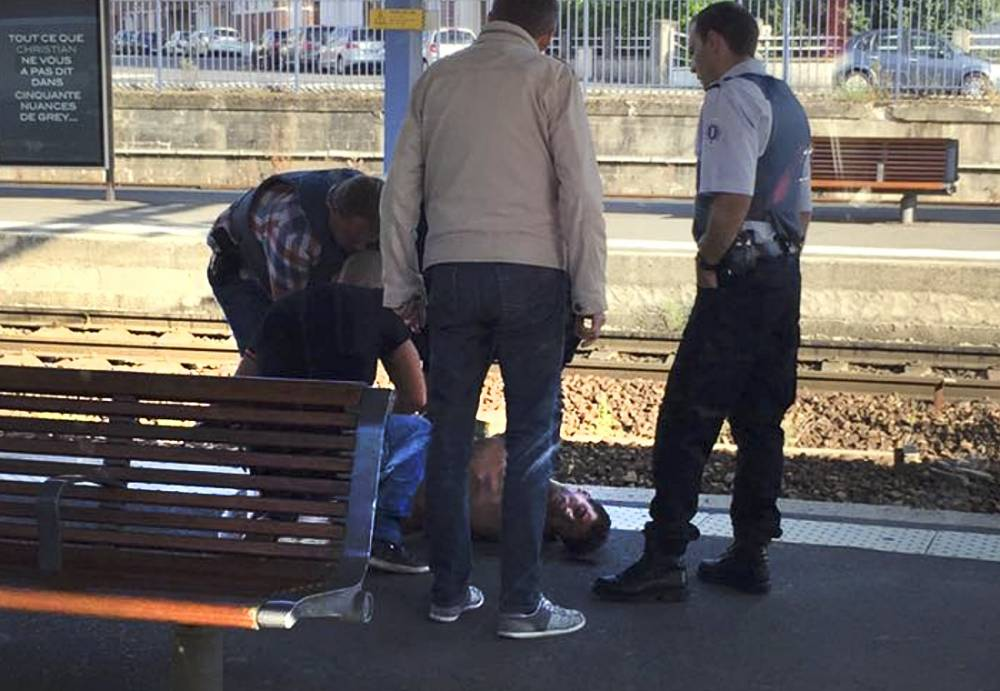 French police stand over a man who is apprehended on the platform at the Arras train station after after shots were fired on the Amsterdam to Paris Thalys high-speed train where several people were injured in Arras, France, August 21, 2015, according to the French interior ministry. A man was arrested when the train stopped at Arras station in northern France but his motives were not yet known, a ministry spokesman said. It is unclear if the man in the picture is the shooter. REUTERS/Christina Cathleen Coons/Handout via ReutersATTENTION EDITORS - THIS PICTURE WAS PROVIDED BY A THIRD PARTY. THIS PICTURE WAS PROCESSED BY REUTERS TO ENHANCE QUALITY. AN UNPROCESSED VERSION WILL BE PROVIDED SEPARATELY. REUTERS IS UNABLE TO INDEPENDENTLY VERIFY THE AUTHENTICITY, CONTENT, LOCATION OR DATE OF THIS IMAGE. NO SALES. NO ARCHIVES. FOR EDITORIAL USE ONLY. NOT FOR SALE FOR MARKETING OR ADVERTISING CAMPAIGNS. MANDATORY CREDIT.