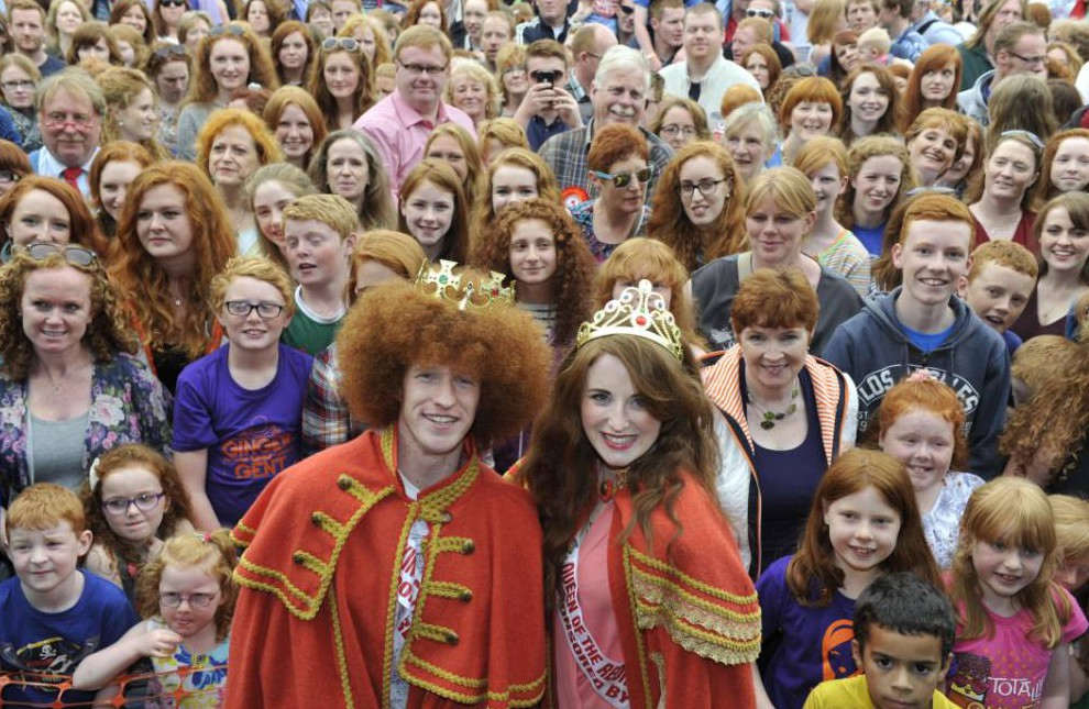 CORK, IRELAND - AUGUST 22: Newly crowned Redhead King and Queen, Alan Reidy and Grainne Keena pose with a crowd full of red heads at the Irish Redhead Convention which celebrates everything to do with red hair held in the village of Crosshaven on August 22, 2015 in Cork, Ireland. Some of the events include the coronation of the Redhead King and Queen, Carrot-tossing, ginger speed-dating, best red beard, best red dog, freckle counting and a redhead parade. The Convention began as a friendly joke between redheaded siblings Joleen and Denis Cronin and also serves as a fundraiser for the Irish Cancer Society raising awareness about skin cancer and melanoma. Red hair is the rarest of hair colours and accounts for just 0.6% of the global population. Ireland has the second highest per capita population of redheads at 10%, next only to Scotland at 13%. The United States is believed to have less than 2% of redheads. (Photo by Clodagh Kilcoyne/Getty Images) *** BESTPIX ***
