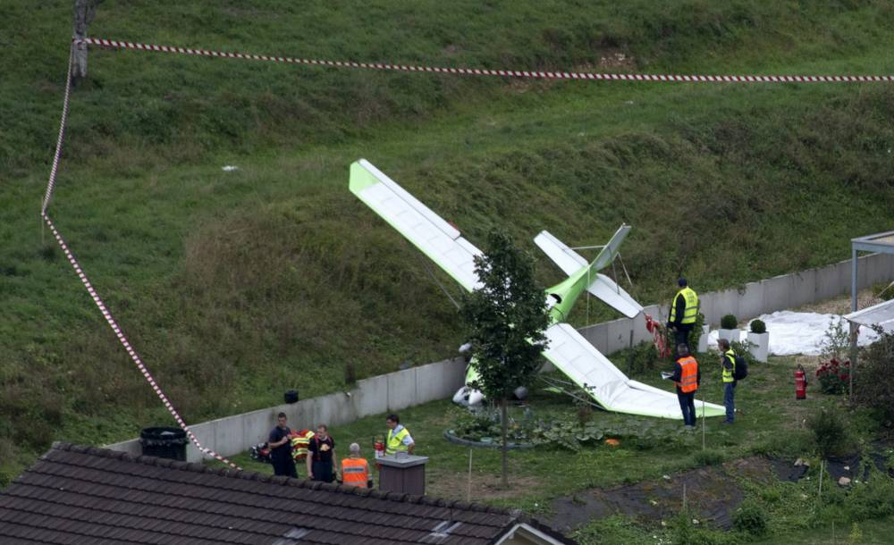epa04894411 A small plane on the ground at the scene of a crash in Dittingen, Switzerland, 23 August 2015. One pilot was reported dead after two aeroplanes from a German stunt flying group crashed at a Swiss air show, according to local police. EPA/GEORGIOS KEFALAS