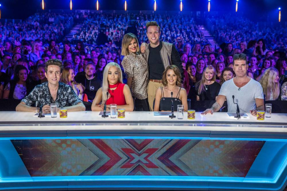Embargoed to 0001 Tuesday August 25 ITV undated handout photo of the new look X Factor 2015 team, presenters (back row) Caroline Flack and Olly Murs with judges (left to right) Nick Grimshaw, Rita Ora, Cheryl Fernandez-Versini and Simon Cowell. The X Factor viewers are to be given even more power this year - choosing for the first time which category the judges will mentor. PRESS ASSOCIATION Photo. Issue date: Tuesday August 25, 2015. A live vote will take place on Twitter while the auditions are airing in which the public will decide whether Simon Cowell, Cheryl Fernandez-Versini, Rita Ora and Nick Grimshaw will mentor the Boys, the Girls, the Overs or the Groups for the rest of the series. See PA story SHOWBIZ XFactor. Photo credit should read: ITV/PA Wire NOTE TO EDITORS: This handout photo may only be used in for editorial reporting purposes for the contemporaneous illustration of events, things or the people in the image or facts mentioned in the caption. Reuse of the picture may require further permission from the copyright holder.