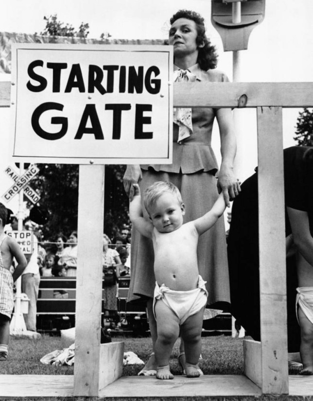 Une mère tient les mains de son bébé dans les starting-blocks pour la course de bébés, ou 'Diaper Derby' de Palisades Park, dans le New Jersey, NJ. (Photo by Keystone-FranceGamma-Rapho via Getty Images)