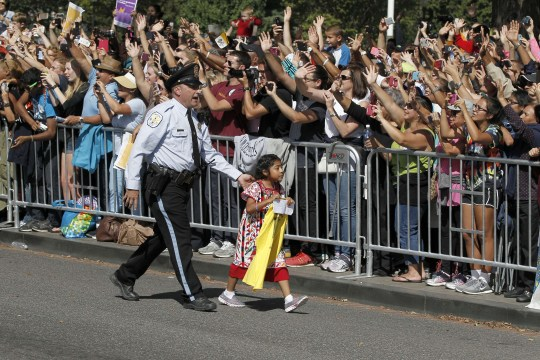 Five-year-old Sofia Cruz is walked back before Pope Francis called for her during the parade (Picture: AFP/Getty Images)