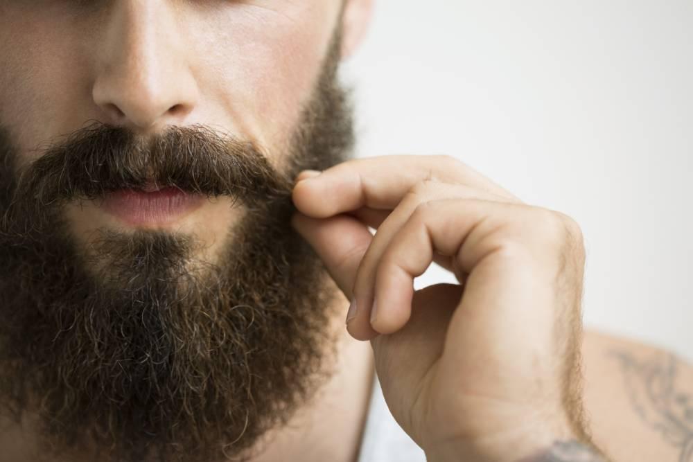 Close up of man touching mustache