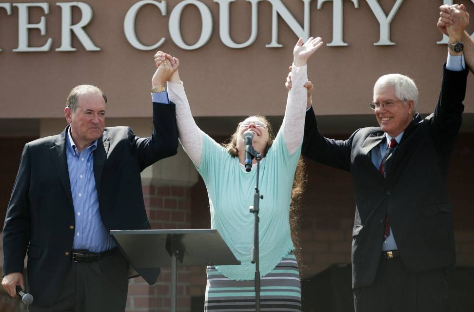 GRAYSON, KY - SEPTEMBER 8: Rowan County Clerk of Courts Kim Davis holds her hands in the air with her attorney Mat Staver (R) and Republican presidential candidate Mike Huckabee in front of the Carter County Detention Center on September 8, 2015 in Grayson, Kentucky. Davis was ordered to jail last week for contempt of court after refusing a court order to issue marriage licenses to same-sex couples. (Photo by Ty Wright/Getty Images) *** BESTPIX ***