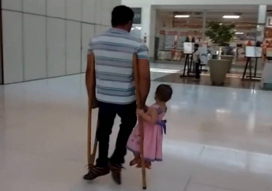 Disabled Manoel Izo may not be able to carry his daughter in the normal way when they are on the move, but he can still give her a lift on his crutches.