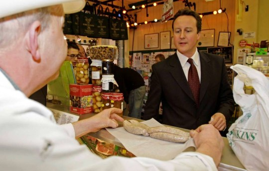 David Cameron looks intently at butcher Robin John Jenkins as he visits the pork counter of a food market in Cheltenham (file pic). hashtag piggate has become the number 1 trending topic worldwide after a biography of the PM alledged an incident with a pig head.