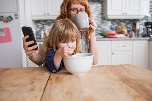 Girl eating breakfast, mother drinking coffee & looking at smartphone