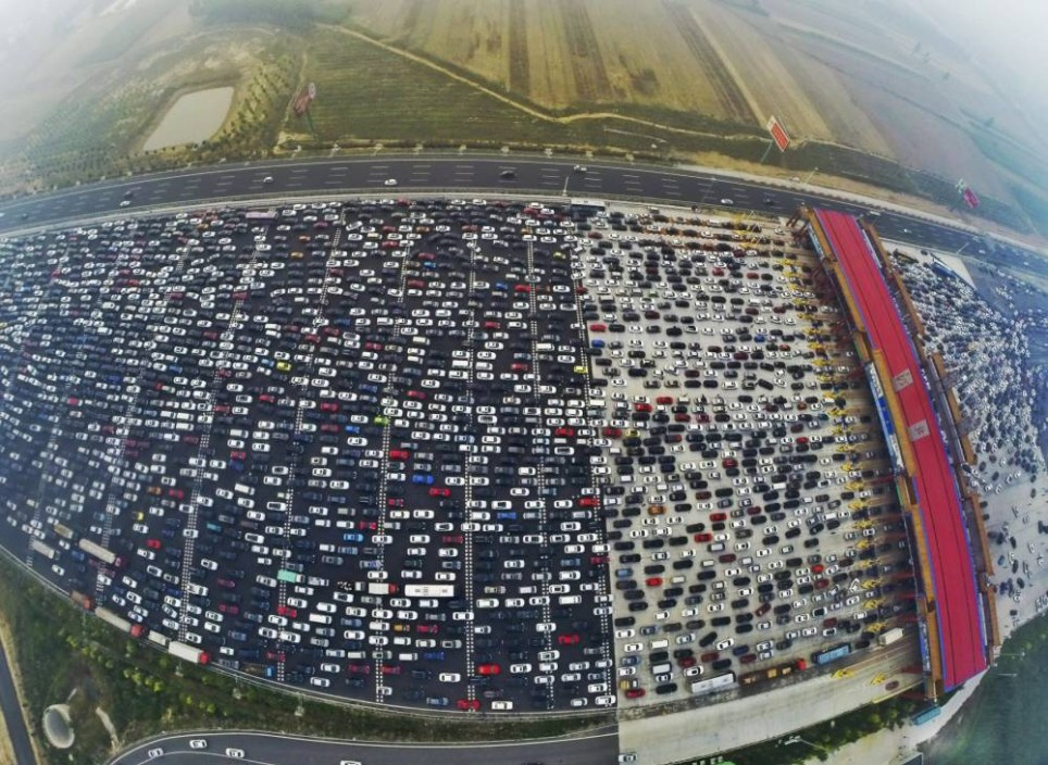 Vehicles are seen stuck in a traffic jam near a toll station as people return home at the end of a week-long national day holiday, in Beijing, China, October 6, 2015. Picture taken October 6, 2015. REUTERS/China Daily CHINA OUT. NO COMMERCIAL OR EDITORIAL SALES IN CHINA